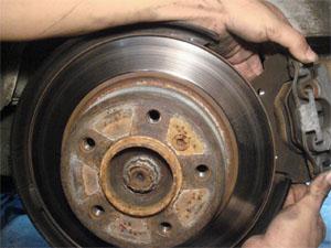 Поднимите машину на домкрате и снимите оригинальный суппорт и тормозные шланги.